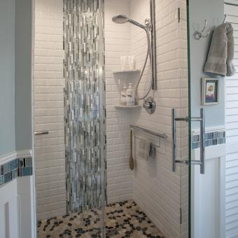 Glass Accent Mimics a Waterfall Cascading onto the Pebble Shower Floor