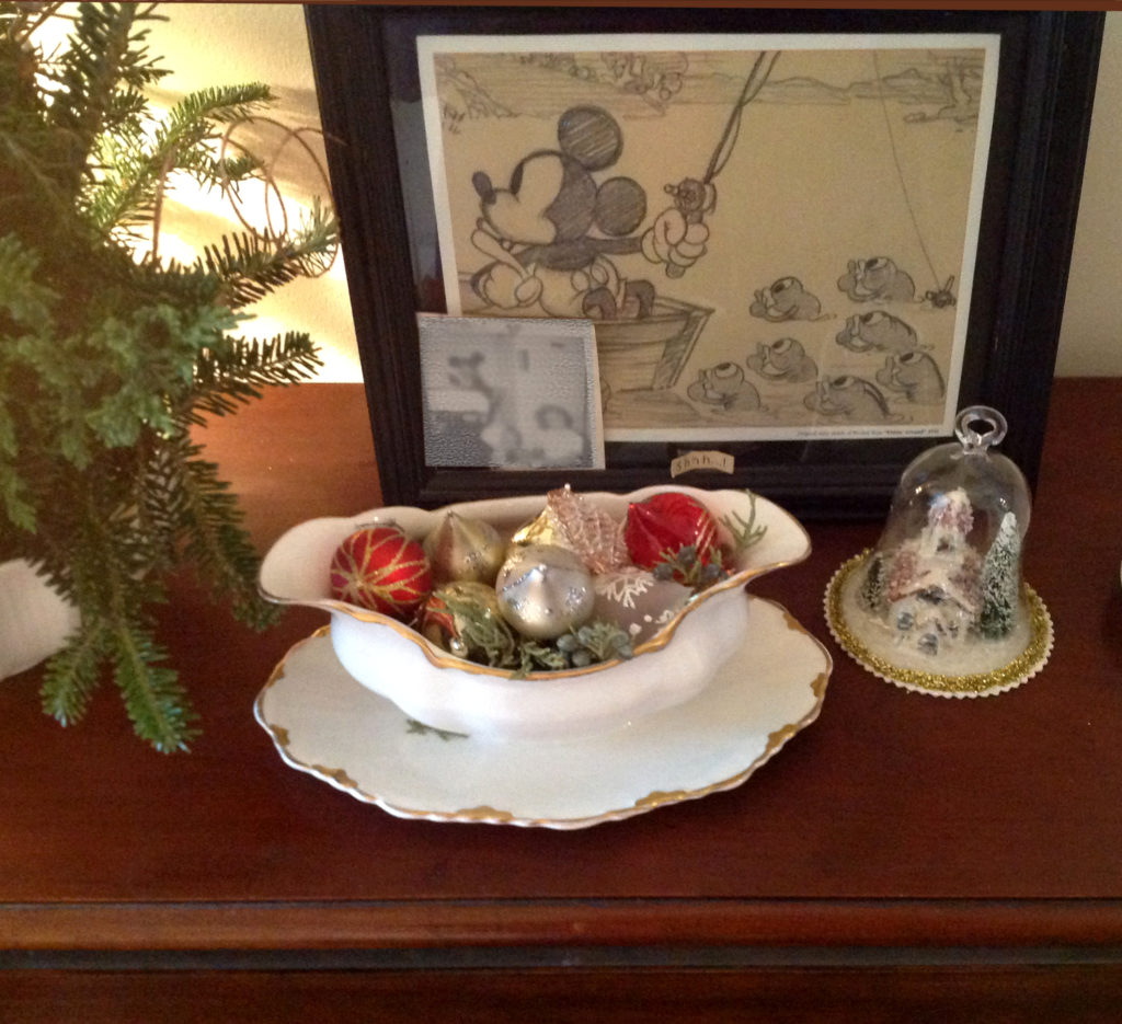 This vintage winter scene is displayed under a glass cloche. The vintage glass ornaments are shown in a gold rimmed bowl with matching saucer.